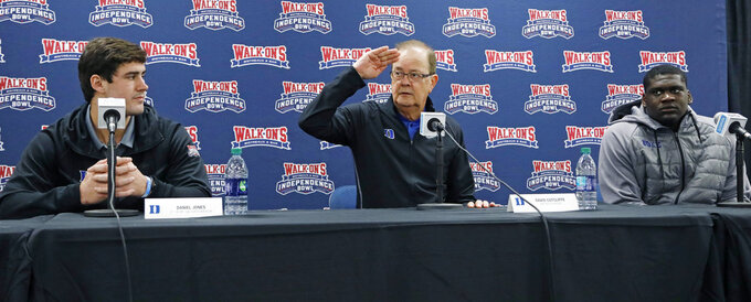 Duke football coach David Cutcliffe, center, salutes the staff of the Independence Bowl for their years' of service to the postseason football game, while quarterback Daniel Jones, left, and defensive tackle Derrick Tangelo, right, listen, at the 2018 Independence Bowl news conference in Shreveport, La., Wednesday, Dec. 26, 2018. Duke faces Temple in the NCAA college football game Thursday. (Rogelio V. Solis/AP)