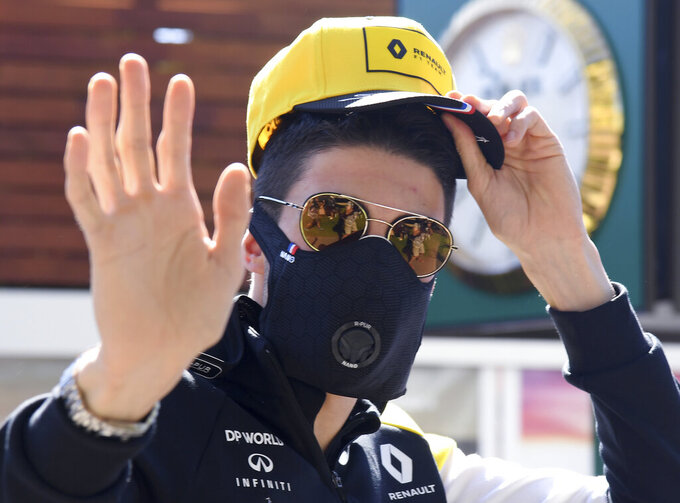 Renault driver Esteban Ocon of France waves as he arrives wearing a mask to the Australian Formula One Grand Prix in Melbourne, Thursday, March 12, 2020. (AP Photo/Andy Brownbill)