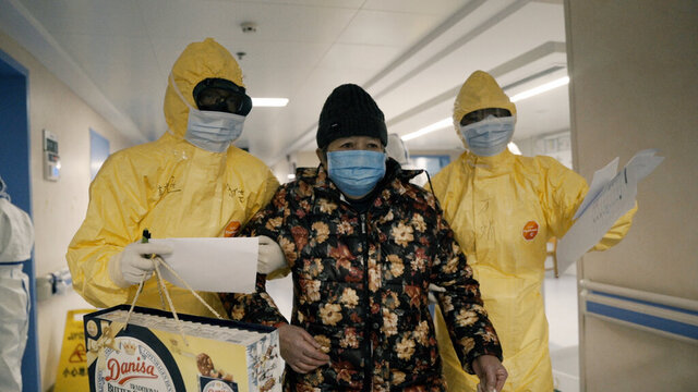 An elderly woman with COVID-19, center, is escorted by two nurses after being admitted to a hospital in Wuhan, China in a scene from the documentary