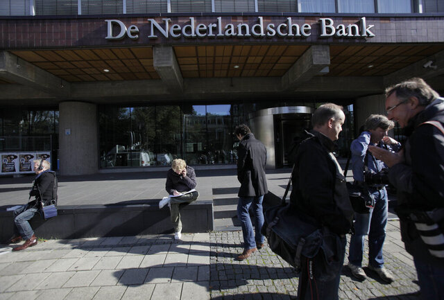 FILE - IN this Monday, Oct. 12, 2009 file photo, reporters wait outside the De Nederlandsche Bank, the Dutch national bank, in Amsterdam, Netherlands. The Netherlands' central bank has moved its Dutch-based stock of gold from its headquarters in Amsterdam to a safe in the nearby city of Haarlem. The 14,000 bars and about 1,000 boxes of gold coins worth a total of some 10 billion euros ($11.7 billion) were transported in a meticulously and closely guarded operation that ended Saturday, Oct. 3, 2020. (AP Photo/Peter Dejong, File)