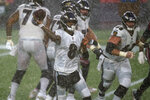 Baltimore Ravens quarterback Lamar Jackson passes during torrential rain in the second half of an NFL football game against the New England Patriots, Sunday, Nov. 15, 2020, in Foxborough, Mass. (AP Photo/Elise Amendola)