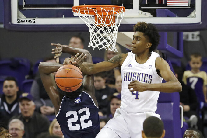 Washington's Jaden McDaniels (4) tangles with Mount St. Mary's Nana Opoku near the rim during the second half of an NCAA college basketball game Tuesday, Nov. 12, 2019, in Seattle. Washington won 56-46. (AP Photo/Elaine Thompson)