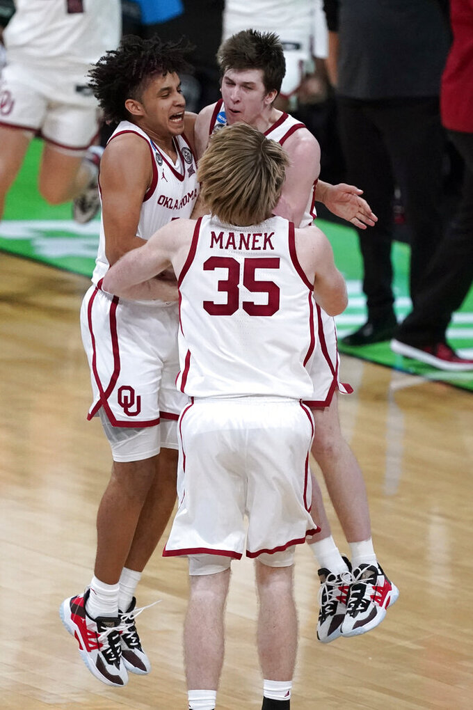 Oklahoma forward Jalen Hill, left, celebrates with teammates Austin Reaves, right, and Brady Manek (35) after a first-round game against Missouri in the NCAA men's college basketball tournament at Lucas Oil Stadium, Saturday, March 20, 2021, in Indianapolis. Oklahoma won 72-68. (AP Photo/Darron Cummings)