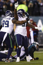Seattle Seahawks' Jarran Reed (90) celebrates with Quinton Jefferson (99) after Philadelphia Eagles' Josh McCown was sacked during the second half of an NFL wild-card playoff football game, Sunday, Jan. 5, 2020, in Philadelphia. (AP Photo/Matt Rourke)