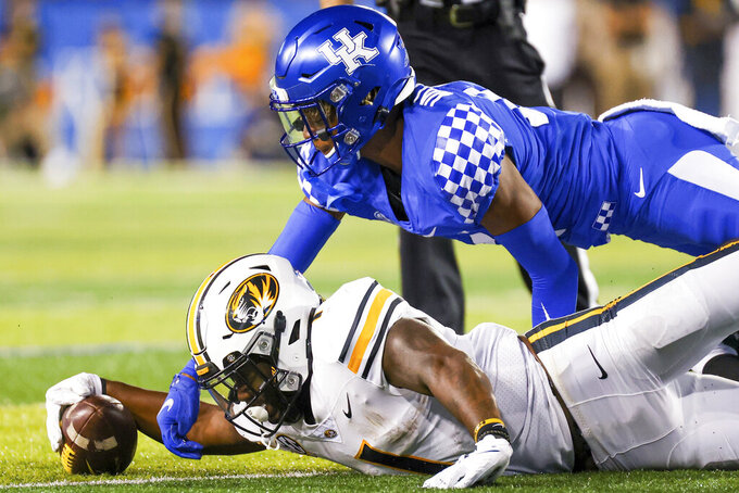 Kentucky defensive back Carrington Valentine, top, tackles Missouri running back Tyler Badie during the second half of an NCAA college football game in Lexington, Ky., Saturday, Sept. 11, 2021. (AP Photo/Michael Clubb)