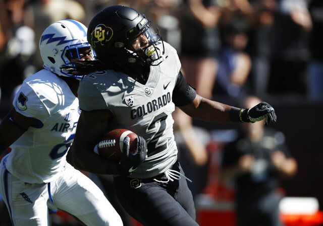 FILE - In this Sept. 14, 2019, file photo, Colorado wide receiver Laviska Shenault Jr., front, outruns Air Force defensive back Zane Lewis to the end zone for a touchdown in the first half of an NCAA college football game in Boulder, Colo. The NFL's shutdown because of the coronavirus pandemic is denying teams the opportunity to get face time with draft prospects who have been injured, have checkered pasts or are under the radar. Shenault Jr. looked like a first-round pick after his breakout season in 2018. His health, coupled with his production falling off last year, might keep him on the board longer than he expected.  (AP Photo/David Zalubowski, File)