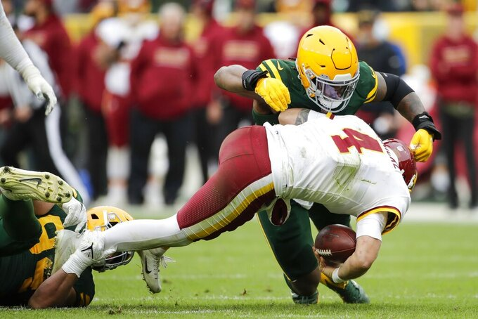 Green Bay Packers' Dean Lowry and Rashan Gary sack Washington Football Team's Taylor Heinicke during the second half of an NFL football game Sunday, Oct. 24, 2021, in Green Bay, Wis. The Packers won 24-10. (AP Photo/Aaron Gash)