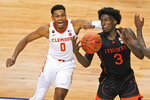 Miami center Nysier Brooks (3) tries to corral a rebound in front of Clemson guard Clyde Trapp (0) during the second half of an NCAA college basketball game in the second round of the Atlantic Coast Conference tournament in Greensboro, N.C., Wednesday, March 10, 2021. (AP Photo/Gerry Broome)