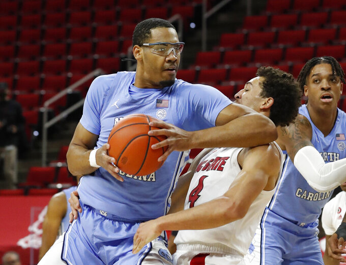 North Carolina's Garrison Brooks (15) fouls North Carolina State's Jericole Hellems (4) during the first half of an NCAA college basketball game in Raleigh, N.C., Tuesday, Dec. 22, 2020 (Ethan Hyman/The News & Observer via AP)