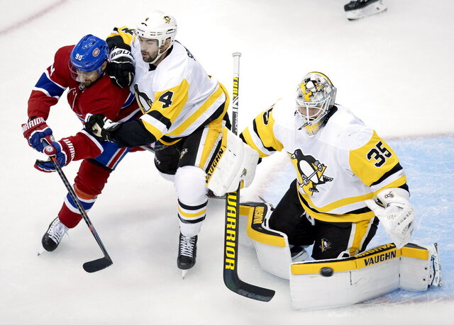 Pittsburgh Penguins defenseman Justin Schultz (4) tries to handle Montreal Canadiens left wing Tomas Tatar (90) as Penguins goaltender Tristan Jarry (35) makes a save during the second period of an NHL hockey playoff game Friday, Aug. 7, 2020, in Toronto. (Frank Gunn/The Canadian Press via AP)