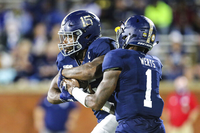 Georgia Southern quarterback Shai Werts (1) hands off the ball to running back J.D. King (15) during the first half of the team's NCAA college football game against South Alabama on Thursday, Oct. 29, 2020, in Statesboro, Ga. (AP Photo/Gary McCullough)