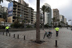 Police bike officers link tape on the empty waterfront promenade as the country starts a new lockdown, in Beirut, Lebanon, Thursday, Jan. 14, 2021. Lebanese authorities began enforcing an 11-day nationwide shutdown and round the clock curfew Thursday, hoping to limit the spread of coronavirus infections spinning out of control after the holiday period. (AP Photo/Bilal Hussein)