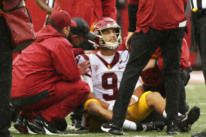 Southern California team staff helps quarterback Kedon Slovis (9) after Slovis was shaken up on a play during the first half of an NCAA college football game against Washington State, Saturday, Sept. 18, 2021, in Pullman, Wash. (AP Photo/Young Kwak)
