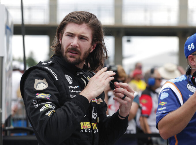 FILE - JR Hildebrand is shown in the pit area during qualifications for the IndyCar Indianapolis 500 auto race at Indianapolis Motor Speedway in Indianapolis, in this Saturday, May 19, 2018, file photo. Hildebrand has a new team and an old-fashioned look for this year's Indianapolis 500. On Thursday, April 8, 2021, A.J. Foyt Racing announced it had hired the California native to drive the No. 1 ABC Supply Chevrolet as the team's fourth driver in IndyCar's biggest race. (AP Photo/Michael Conroy, File)