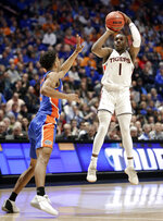 Auburn guard Jared Harper (1) makes a 3-point shot against Florida guard Jalen Hudson in the closing seconds of the second half of an NCAA college basketball game at the Southeastern Conference tournament Saturday, March 16, 2019, in Nashville, Tenn. Auburn won 65-62. (AP Photo/Mark Humphrey)