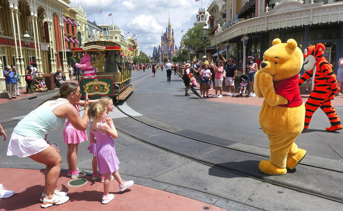 Young guests enjoy seeing Winnie The Pooh, and Tigger too, at the Magic Kingdom at Walt Disney World, in Lake Buena Vista, Fla., Monday, May 17, 2021, after Disney Co. eased face mask requirements over the weekend. Guests are allowed to go maskless in outdoor areas of the parks. Indoor attractions, shops and Disney transportation at the resort all still require masks. (Joe Burbank/Orlando Sentinel via AP)