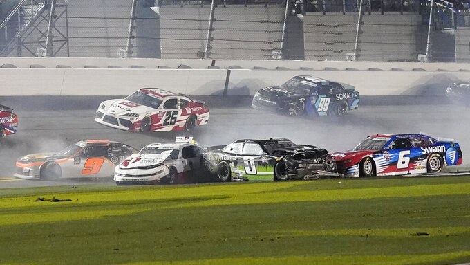 Noah Gragson (9), Michael Annett (1), Jeffrey Earnhardt (0), and Ryan Vargas (6) crash coming out of turn 4 as Brandon Gdovic (26) and Stefan Parsons (99) go high to avoid the wreck during the NASCAR Xfinity Series auto race at Daytona International Speedway, Saturday, Feb. 13, 2021, in Daytona Beach, Fla. (AP Photo/John Raoux)
