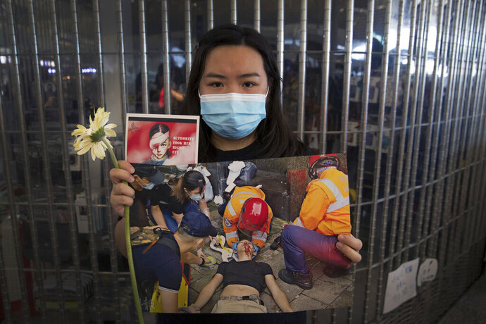 A woman holds a flower and posters showing people injured by police as protesters stage a sit-in rally at he Hong Kong International Airport in Hong Kong, Tuesday, Aug. 13, 2019. Protesters clogged the departure area at Hong Kong's reopened airport Tuesday, a day after they forced one of the world's busiest transport hubs to shut down entirely amid their calls for an independent inquiry into alleged police abuse. (AP Photo/Vincent Thian)