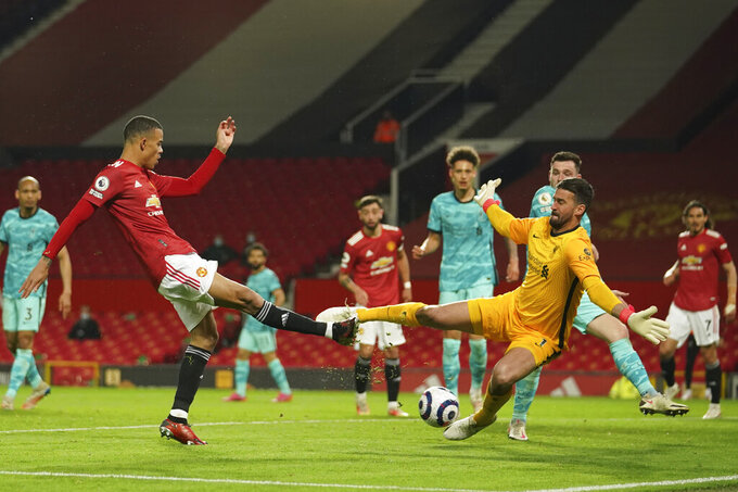 Liverpool's goalkeeper Alisson, right, makes a save in front of Manchester United's Mason Greenwood during the English Premier League soccer match between Manchester United and Liverpool, at the Old Trafford stadium in Manchester, England, Thursday, May 13, 2021. (AP Photo/Dave Thompson,Pool)