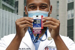 Alister Martin, an emergency room doctor at Massachusetts General Hospital, holds up a voter information card he wears on his ID lanyard, which gives patients a Q-code and text link to help them register to vote, outside the hospital, Friday, Aug. 7, 2020, in Boston. Martin founded the organization