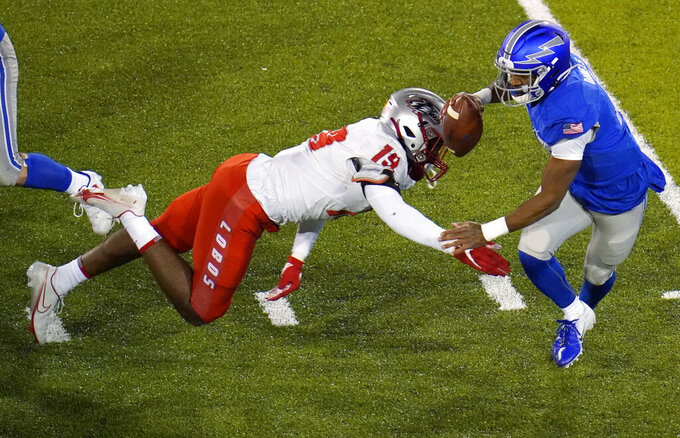 Air Force quarterback Haaziq Daniels, right, gets away from New Mexico linebacker Devin Sanders during the first half of an NCAA college football game Friday, Nov. 20, 2020, at Air Force Academy, Colo. (AP Photo/David Zalubowski)