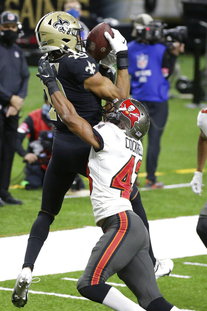 New Orleans Saints wide receiver Tre'Quan Smith, left, makes a touchdown catch in the end zone against Tampa Bay Buccaneers defensive back Ross Cockrell (43) during the second half of an NFL divisional round playoff football game, Sunday, Jan. 17, 2021, in New Orleans. (AP Photo/Butch Dill)