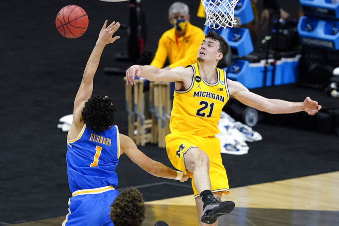 Michigan guard Franz Wagner (21) blocks a shot by UCLA guard Jules Bernard (1) during the first half of an Elite 8 game in the NCAA men's college basketball tournament at Lucas Oil Stadium, Tuesday, March 30, 2021, in Indianapolis. (AP Photo/Darron Cummings)