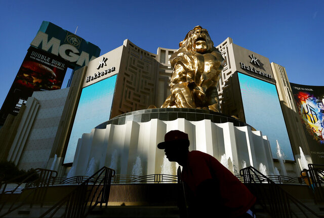 FILE - In this Aug. 3, 2015, file photo, a man rides his bike past the MGM Grand hotel and casino in Las Vegas.   MGM Resorts plans to lay off 18,000 workers as the casino company struggles with the fallout from the pandemic. The Las Vegas-based parent of the Bellagio said in a letter to employees that furloughed employees will keep health benefits until Sept. 30, 2020 according to a report in The Wall Street Journal. (AP Photo/John Locher, File)