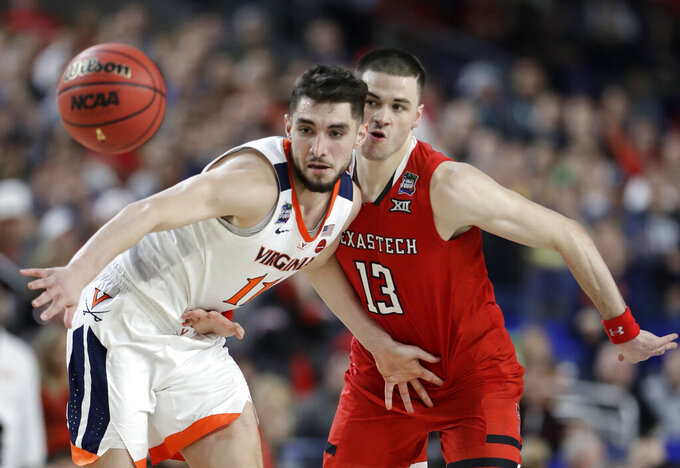 Virginia guard Ty Jerome fights for a loose ball with Texas Tech guard Matt Mooney, right, during the second half in the championship game of the Final Four NCAA college basketball tournament, Monday, April 8, 2019, in Minneapolis. (AP Photo/Jeff Roberson)
