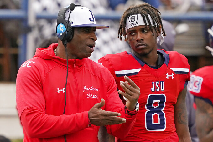 Jackson State football coach Deion Sanders, left, confers with quarterback Quincy Casey (8) during the second half of an NCAA college football game against Edward Waters in Jackson, Miss., Sunday, Feb. 21, 2021. (AP Photo/Rogelio V. Solis)