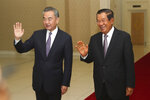 Chinese Foreign Minister Wang Yi, left, waves with Cambodian Prime Minister Hun Sen prior to a meeting at Peace Palace in Phnom Penh, Cambodia, Monday, Oct. 12, 2020. The two countries signed a free trade agreement on Monday. (AP Photo/Heng Sinith)