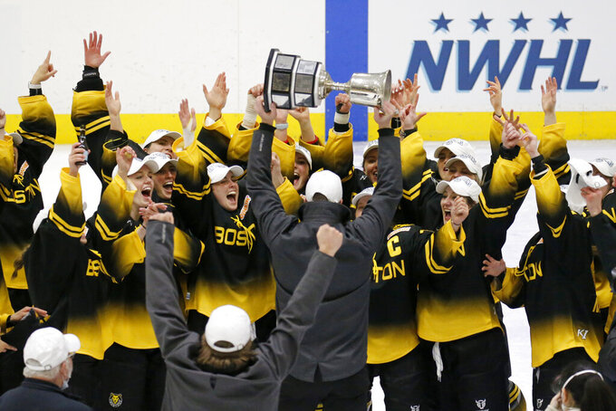 FILE - Boston Pride players cheer as coach Paul Mara hoists the NWHL Isobel Cup trophy after the team's win over the Minnesota Whitecaps in the championship hockey game in Boston, in this Saturday, March 27, 2021, file photo. The National Women's Hockey League made a potentially game-changing decision for the sport in approving to double its salary cap to $300,000 for each of its six teams on Wednesday, April 28, 2021, based on projections it is making strides in achieving financial stability entering its seventh season. (AP Photo/Mary Schwalm, File)