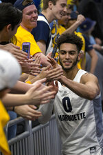 FILE - In this Feb. 9, 2019, file photo, Marquette guard Markus Howard celebrates with fans after defeating Villanova during an NCAA college basketball game in Milwaukee. Howard will leave Marquette as one of the most dynamic scorers in Big East history. He has the most career points of any active Division I player and leads the nation in points per game this season. The one achievement that has eluded the 5-foot-11 senior guard is an NCAA Tournament victory. Howard is seeking one last chance to rectify that as he caps an otherwise illustrious college career. (AP Photo/Darren Hauck, File)