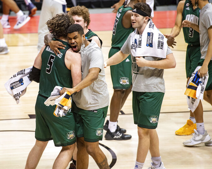 Ohio players celebrate on the court after defeating Virginia in a first-round game in the NCAA men's college basketball tournament, Saturday, March 20, 2021, at Assembly Hall in Bloomington, Ind. (AP Photo/Doug McSchooler)
