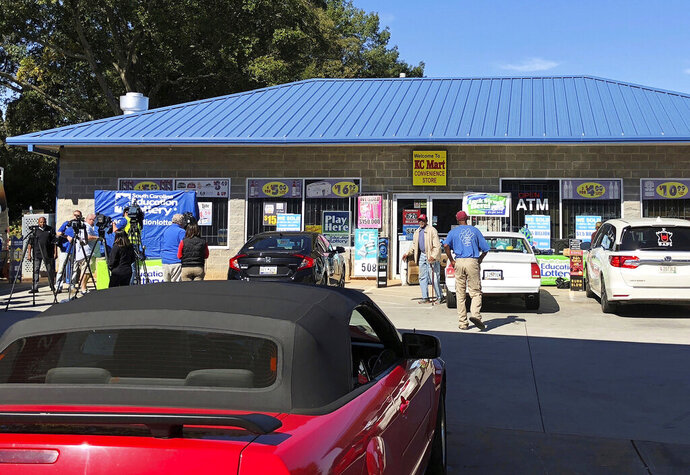 FILE - In this Oct. 24, 2018, file photo, media, left record people entering the KC Mart in Simpsonville, S.C., after it was announced the winning Mega Millions lottery ticket was purchased at the store. Unless the winner chooses to come forward, the world may never know who won. The winner of a $1.537 billion lottery jackpot in South Carolina has yet to come forward. That means the state of South Carolina might be a big loser too. With the prize unclaimed, the state Board of Economic Advisors is expected Thursday, Feb. 14, 2019, to suggest removing the $61 million windfall from the state spending plan. (AP Photo/Jeffrey Collins, File)