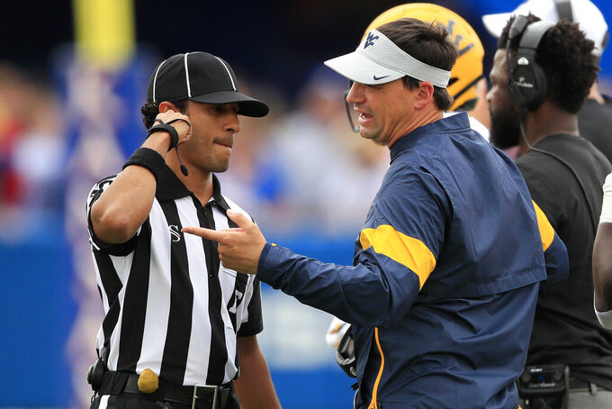 West Virginia head coach Neal Brown, right, talks with field judge Gabriel DeLeon, left, during the first half of an NCAA college football game in Lawrence, Kan., Saturday, Sept. 21, 2019. (AP Photo/Orlin Wagner)
