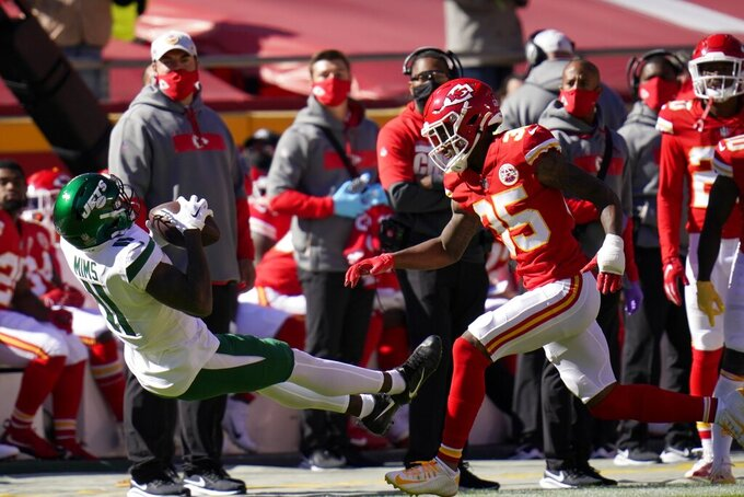 New York Jets wide receiver Denzel Mims (11) falls to the ground in front of Kansas City Chiefs cornerback Charvarius Ward (35) after catching a pass in the first half of an NFL football game on Sunday, Nov. 1, 2020, in Kansas City, Mo. (AP Photo/Jeff Roberson)