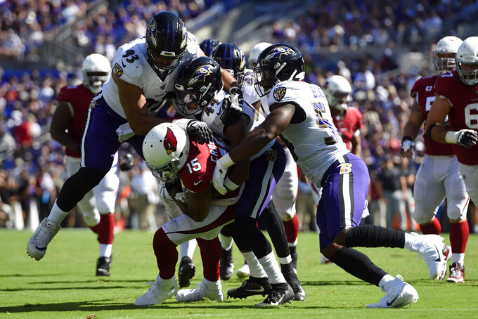 Baltimore Ravens defenders tackle Arizona Cardinals wide receiver Michael Crabtree (15) in the second half of an NFL football game, Sunday, Sept. 15, 2019, in Baltimore. (AP Photo/Gail Burton)