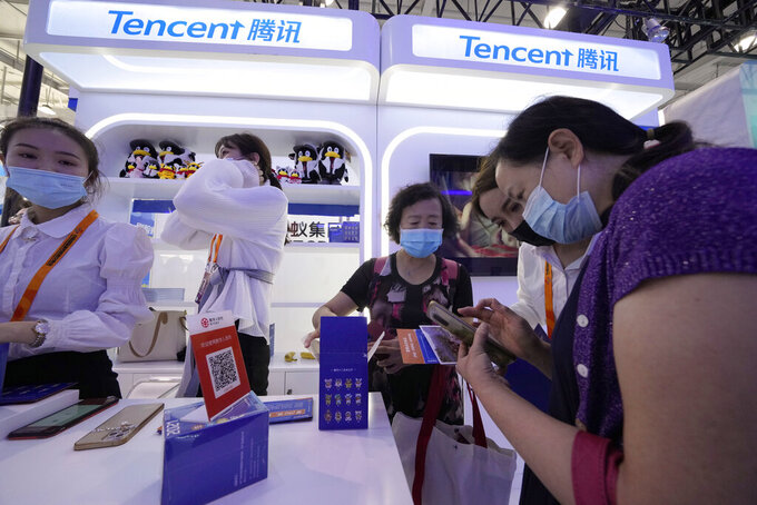 A woman holds up a soft toy at the Tencent booth during the China International Fair for Trade in Services (CIFTIS) in Beijing Monday, Sept. 6, 2021. Beijing has launched anti-monopoly and data security crackdowns to tighten control over internet giants including e-commerce platform Alibaba Group and games and social media operator Tencent Holdings Ltd. that looked too big and potentially independent.(AP Photo/Ng Han Guan)