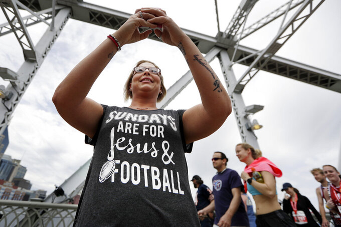 Denver Broncos fan Trina Henderson takes photos on the final day of the NFL football draft Saturday, April 27, 2019, in Nashville, Tenn. (AP Photo/Mark Humphrey)