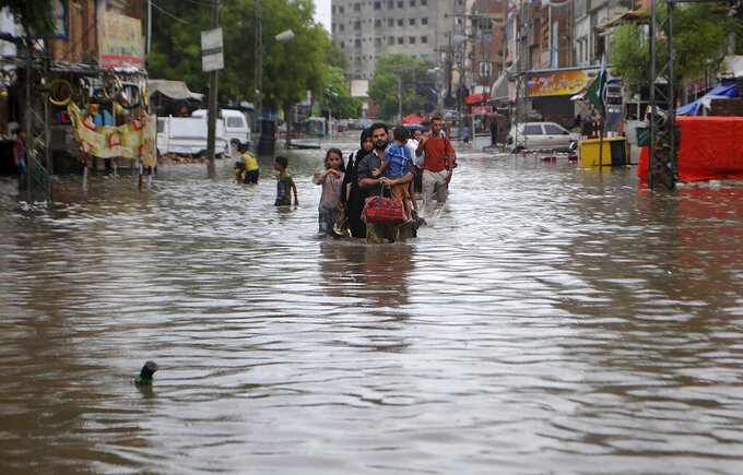 People wade through a flooded road after heavy rainfalls in Hyderabad, Pakistan, Tuesday, Aug. 25, 2020. Three days of monsoon rains have caused the deaths of dozens people and damaged hundreds homes across Pakistan, the country's national disaster management agency said Tuesday. (AP Photo/Pervez Masih)