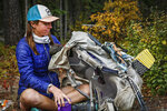 Sarah Williams, 29, of Kalispell, Mont., repacks her backpack on Camas Creek Road in Glacier National Park, Mont., on Sept. 23, 2020. Williams was near the end of her walk of the Continental Divide Trail, a route that leads from the Mexican Border to the Canadian border. (Hunter D'Antuono/Flathead Beacon via AP)