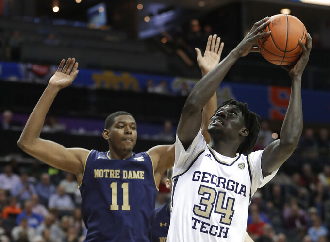 Georgia Tech's Abdoulaye Gueye (34) shoots against Notre Dame's Juwan Durham (11) during the first half of an NCAA college basketball game in the Atlantic Coast Conference tournament in Charlotte, N.C., Tuesday, March 12, 2019. (AP Photo/Nell Redmond)
