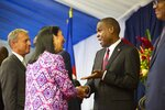 CORRECTS TO REMOVE EXACT NUMBER OF U.S. CONTRACTORS ARRESTED - FILE - In this Aug. 7, 2018 file photo, Haiti's Prime Minister Jean-Henry Ceant shakes hands with U.S. ambassador in Haiti, Michele Sison, at the National Palace in Port-au-Prince, Haiti. Neither the Haitian government nor the American ambassador has offered any explanation of the Feb. 17, 2019 arrest of a group of U.S. contractors' or the reason for their release, which appeared to violate Haitian criminal procedure. (AP Photo/Dieu Nalio Chery, File)