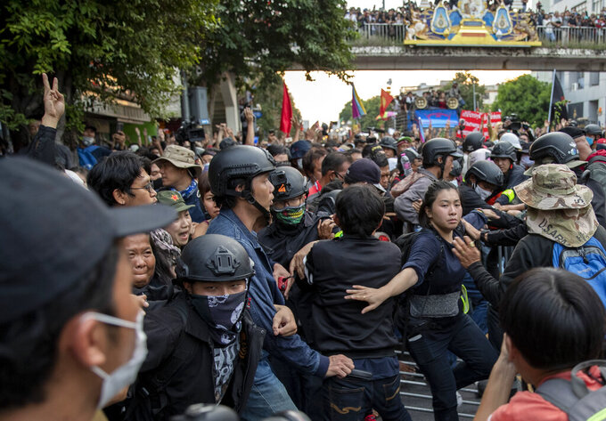 Pro-democracy protesters remove barriers and march forward during a street march in Bangkok, Thailand, Wednesday, Oct. 14, 2020. Thousands of anti-government protesters gathered Wednesday for a rally being held on the anniversary of a 1973 popular uprising that led to the ousting of a military dictatorship, amid a heavy police presence and fear of clashes with political opponents. (AP Photo/Gemunu Amarasinghe)