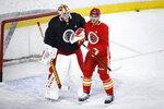Calgary Flames' Mikael Backlund, right, jokes with goalie Jacob Markstrom during NHL hockey practice in Calgary, Alberta, Tuesday, Jan. 5, 2021. (Jeff McIntosh/The Canadian Press via AP)