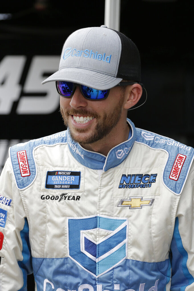 Ross Chastain smiles on pit road before practice for a NASCAR Truck Series auto race on Friday, Nov. 15, 2019, at Homestead-Miami Speedway in Homestead, Fla. Chastain is one of four drivers racing for the series championship. (AP Photo/Terry Renna)