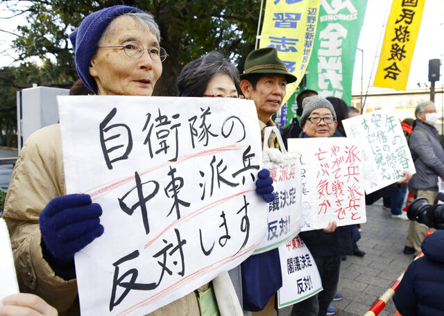 People hold placards protesting against a troop dispatch to Middle East outside the prime minister's official residence in Tokyo Friday, Dec. 27, 2019. Japan on Friday approved a contentious plan to send its naval troops to the Middle East to contribute to the peace and stability in the area and ensure the safety of Japanese ships transporting oil, a mission crucial to an energy-poor country that heavily depends on oil imports from the region. The placard at left reads: