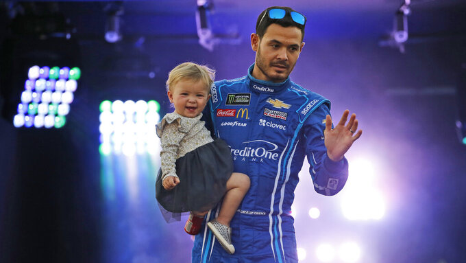 Kyle Larson and his daughter greet fans during driver introductions for the NASCAR Monster Energy Cup series auto race at Richmond Raceway in Richmond, Va., Saturday, Sept. 21, 2019. (AP Photo/Steve Helber)