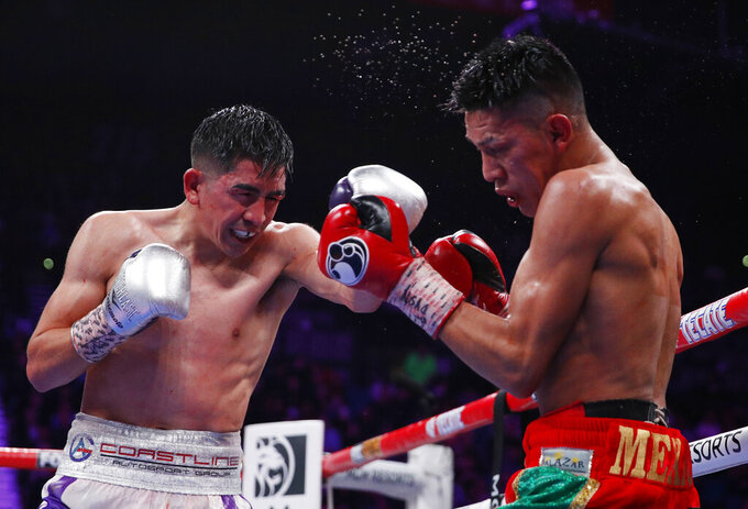 FILE - In this Nov. 23, 2019, file photo, Leo Santa Cruz, left, hits Miguel Flores during their WBA super featherweight title bout in Las Vegas. Gervonta Davis wants to become a pay-per-view star, much like his promoter and mentor Floyd Mayweather Jr. was in his prime. He also wants to fight in front of a lot of screaming fans, though he'll have to settle for a pandemic-limited audience of ticket holders Saturday in San Antonio for his title matchup with veteran Leo Santa Cruz. (AP Photo/John Locher, File)